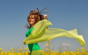 femme-heureuse-bras-en-l-air-voile-vert-fleurs-jaunes-ciel-bleu