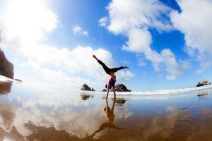 photo-femme-acrobatie-plage-ciel-bleu-mais-nuages